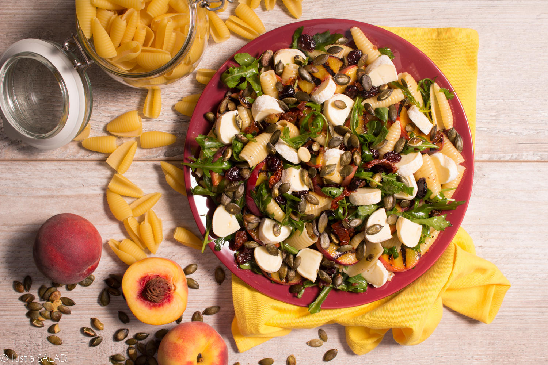 Sałatka z makaronem, brzoskwinią, żurawiną, camembertem, pestkami dyni i suszonymi pomidorami.