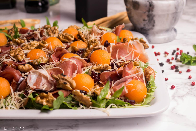 Sałatka z rukolą, szynką parmeńską, parmezanem, melonem, suszoną żurawiną i orzechami włoskimi.