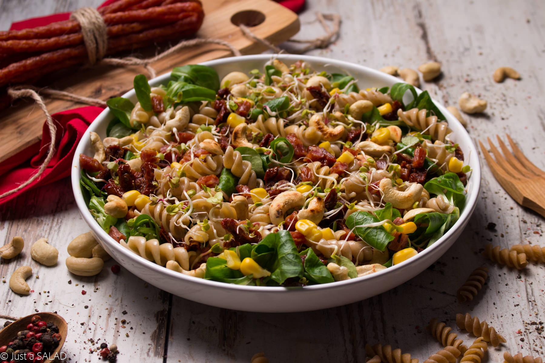 Sałatka z kabanosem, roszponką, kukurydzą, suszonymi pomidorami, makaronem, kiełkami rzodkiewki i nerkowcami.
