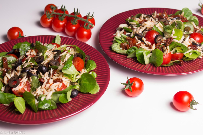 Sałatka z roszponką, makaronem, oliwkami, pestkami dyni i słonecznika oraz pomidorami suszonymi i koktajlowymi.