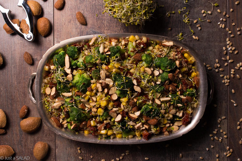 Sałatka z pęczakiem, brokułem, kiełkami brokuła, kukurydzą, suszonymi pomidorami, migdałami i curry.
