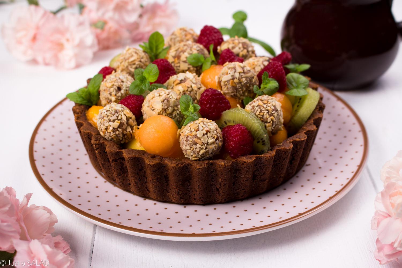 Sałatka deserowa z owocami i słodkimi kuleczkami podana w wafelkowej miseczce.