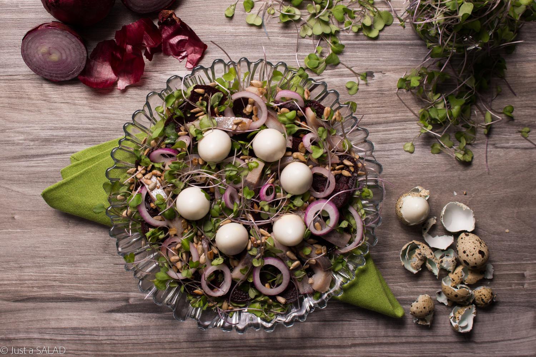 Sałatka ze śledziem, jajeczkami, burakiem, listkami jarmużu i pestkami słonecznikowymi.