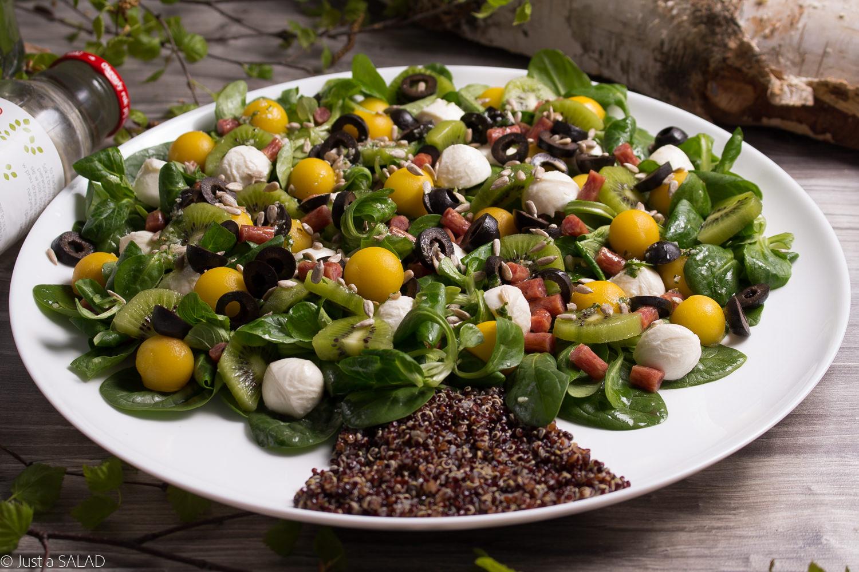 Sałatka z komosą ryżową, liśćmi szpinaku, roszponką, mango, kiwi, kabanosami, mozzarellą, oliwkami i pestkami słonecznika.