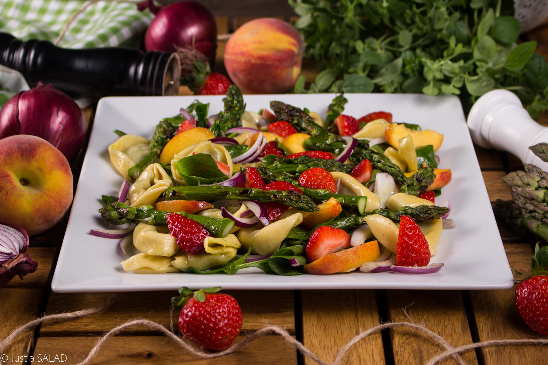 Sałatka ze szpinakiem, tortelloni, szparagami, czerwoną cebulą, brzoskwiniami i truskawkami.
