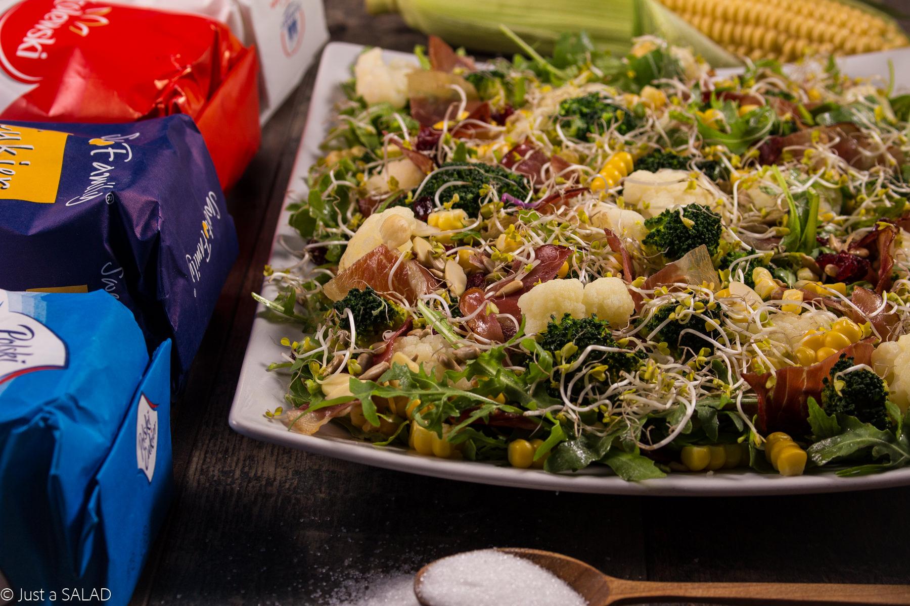 WARZYWA Z CUKREM. Sałatka z brokułami, kalafiorem, kukurydzą, chipsami z szynki parmeńskiej i bakaliami.