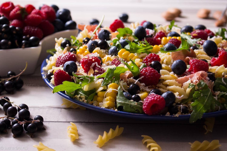 Wielkie świętowanie lata. Sałatka z makaronem, rukolą, porzeczkami, malinami, borówkami, kukurydzą, szynką serrano, kozią fetą i migdałami.