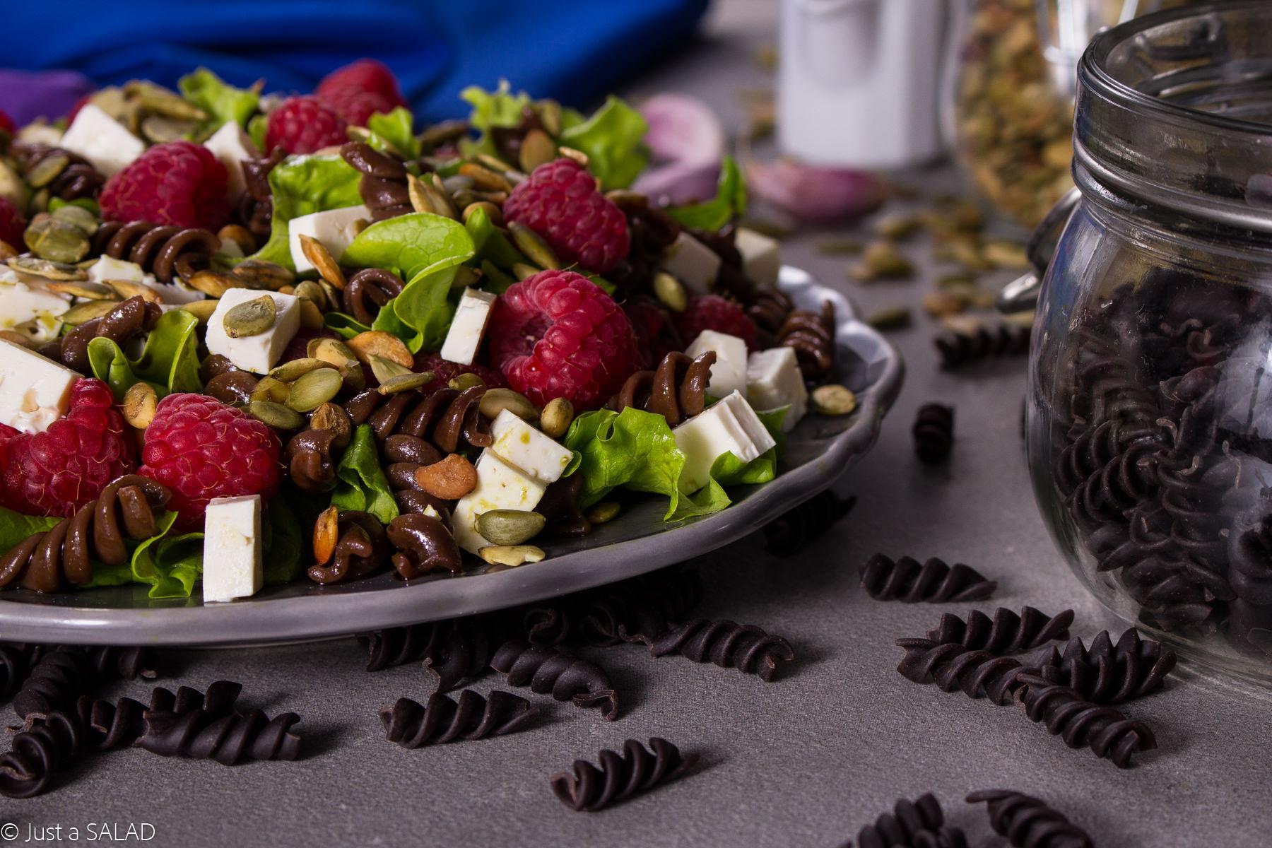Sałatka z makaronem czekoladowym, mixem sałat, malinami, kozim serem, pestkami dyni oraz dyniowym dressingiem.