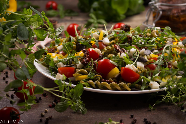 NIEZŁE ZIÓŁKO. Sałatka z makaronem, rukolą, papryką, pomidorkami koktajlowymi i suszonymi, pestkami dyni, kozim serem i ziołowym pesto.