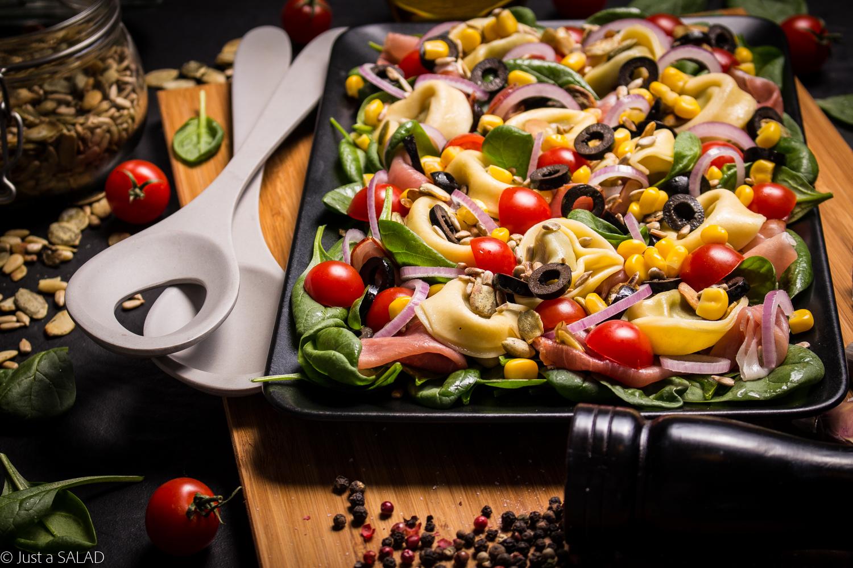 OD UCHA DO UCHA. Sałatka z tortellini, szpinakiem, szynką dojrzewającą, pomidorkami, kukurydzą, oliwkami, czerwoną cebulą oraz pestkami dyni i słonecznika.