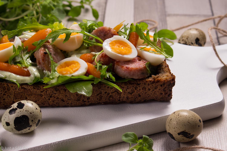 A'la ŻUREK. Sałatka z białą kiełbasą, jajeczkami przepiórczymi, marchewką baby, rukolą i sosem na bazie majeranku podana na żytnim chlebie.