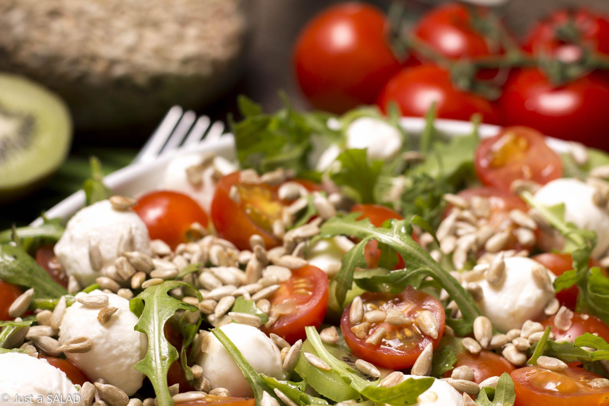 Sałatka z rukolą, kiwi, pomidorami koktajlowymi, mozzarellą i pestkami słonecznika.