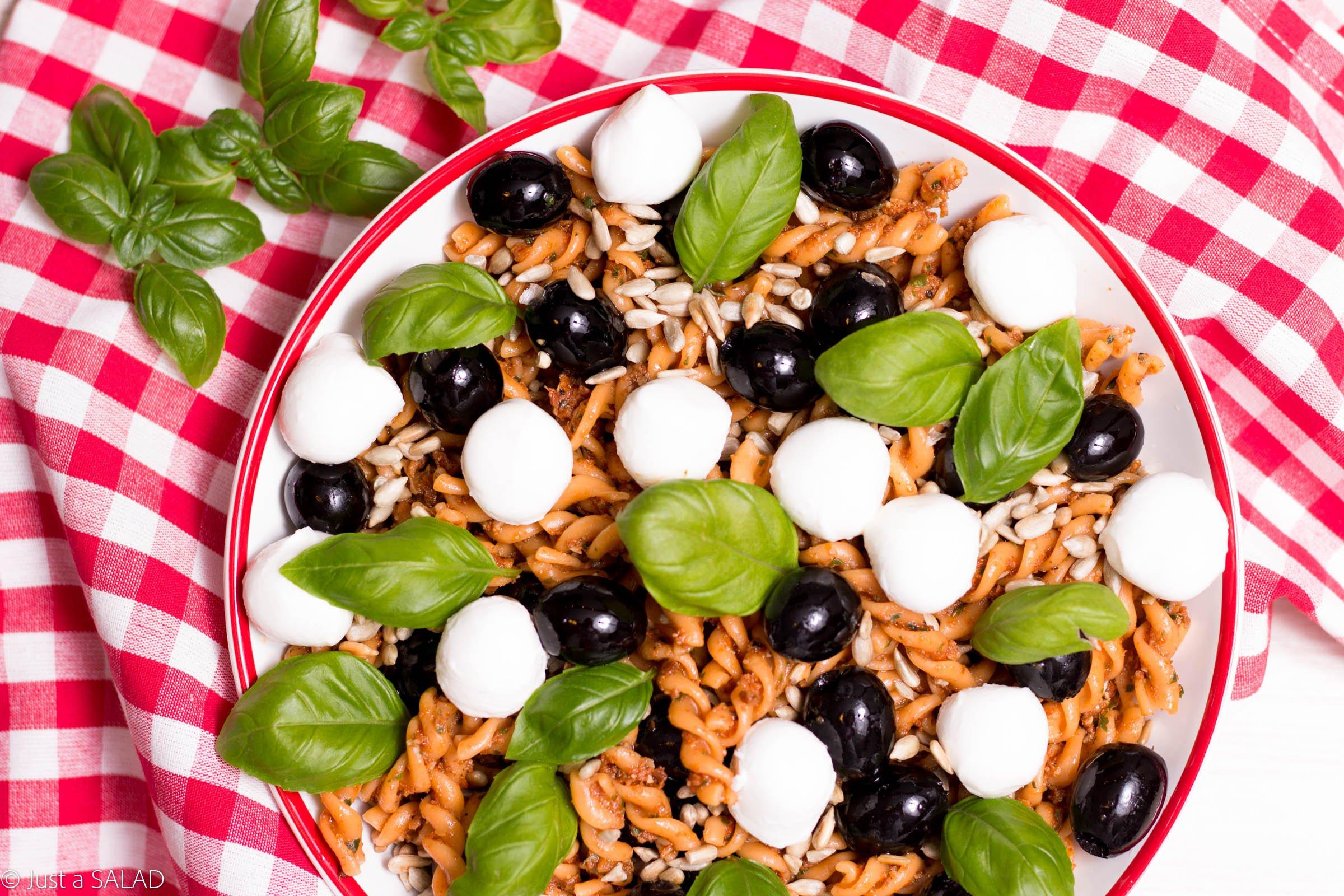Sałatka z makaronem, pesto z suszonych pomidorów, oliwkami, mozzarellą i pestkami słonecznika
