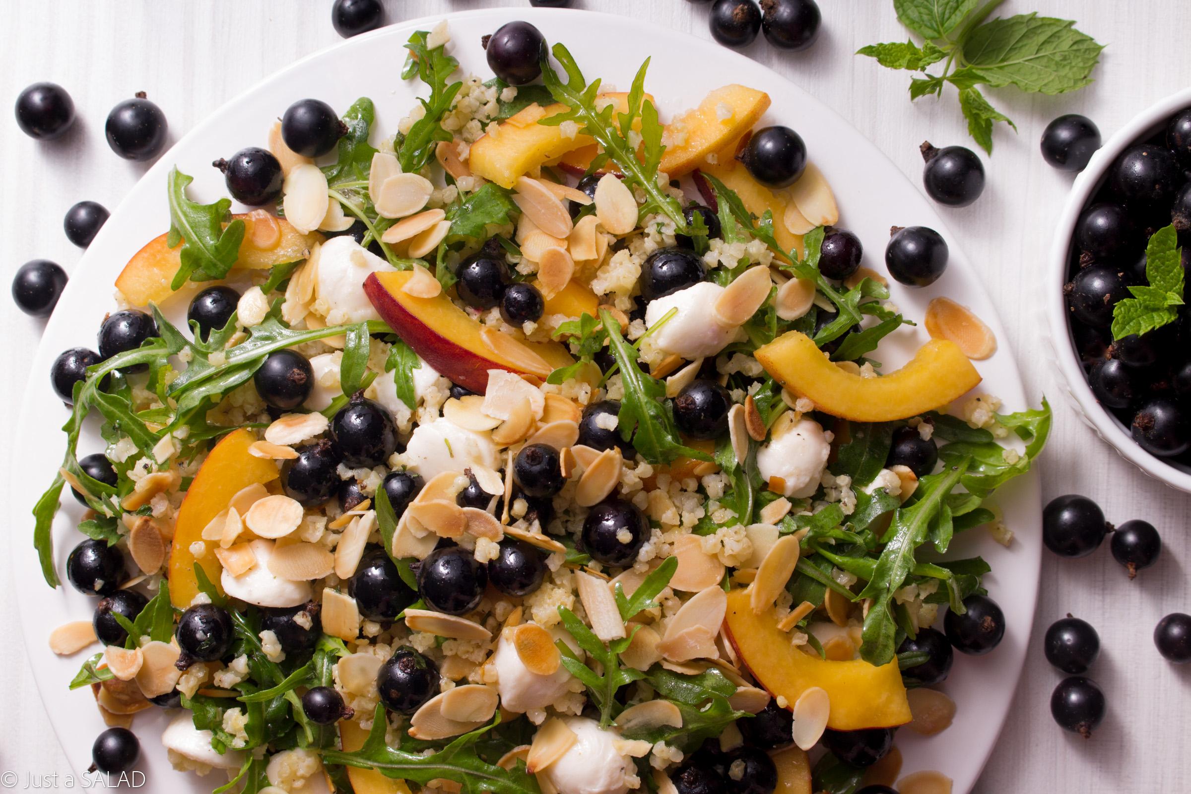 Sałatka z rukolą, kaszą jaglaną, brzoskwinią, czarną porzeczką, mozzarellą i płatkami migdałowymi.