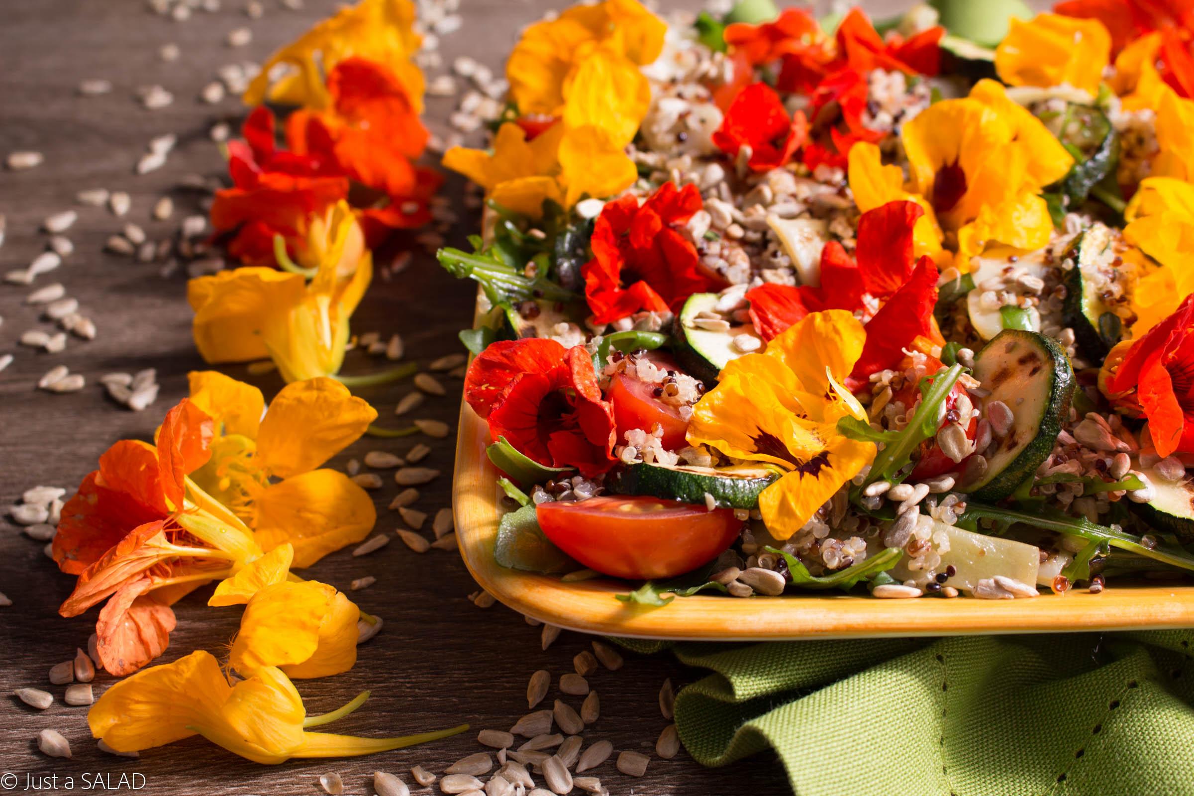 Sałatka z komosą ryżową, rukolą, fasolą mamut, cukinią, pestkami słonecznika i kwiatami nasturcji.