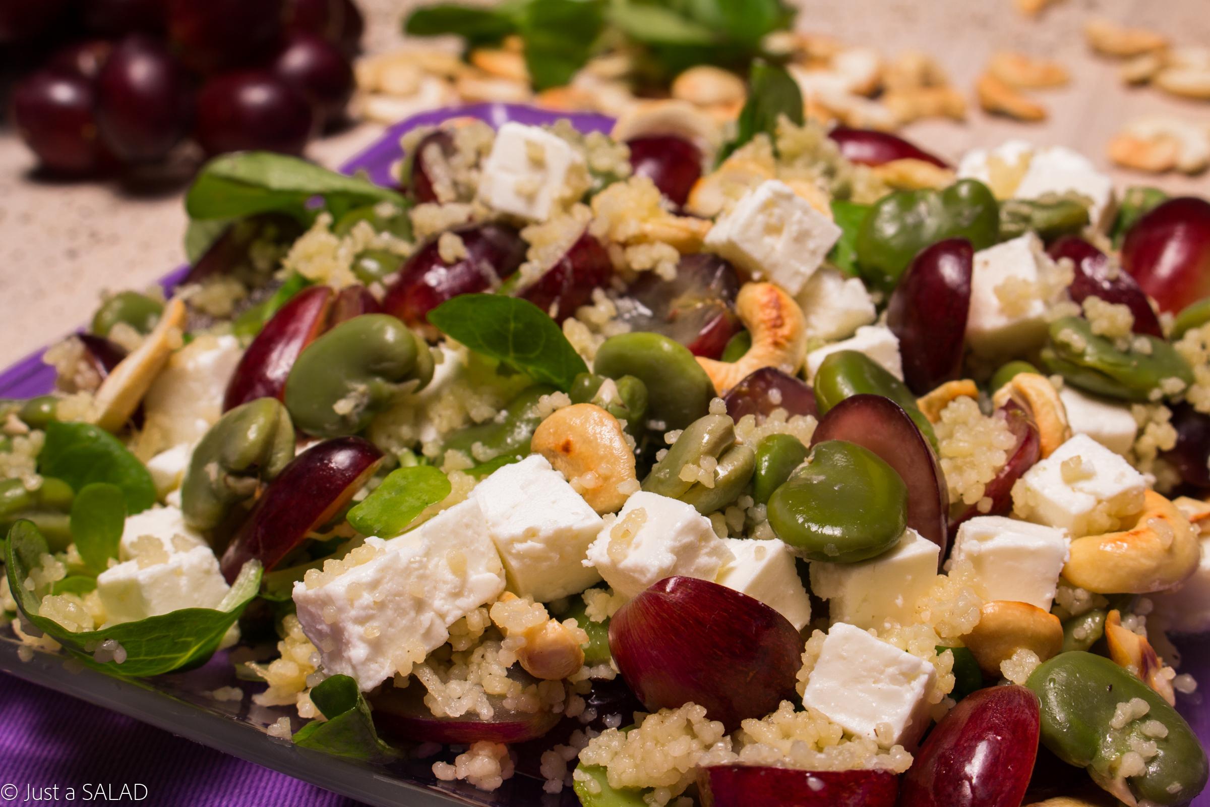 Sałatka z kuskus, bobem, fetą, winogronami, nerkowcami i roszponką.