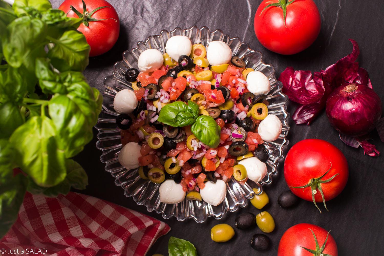 Sałatka z pomidorów, oliwek, czerwonej cebuli, mozzarelli i liści bazylii.
