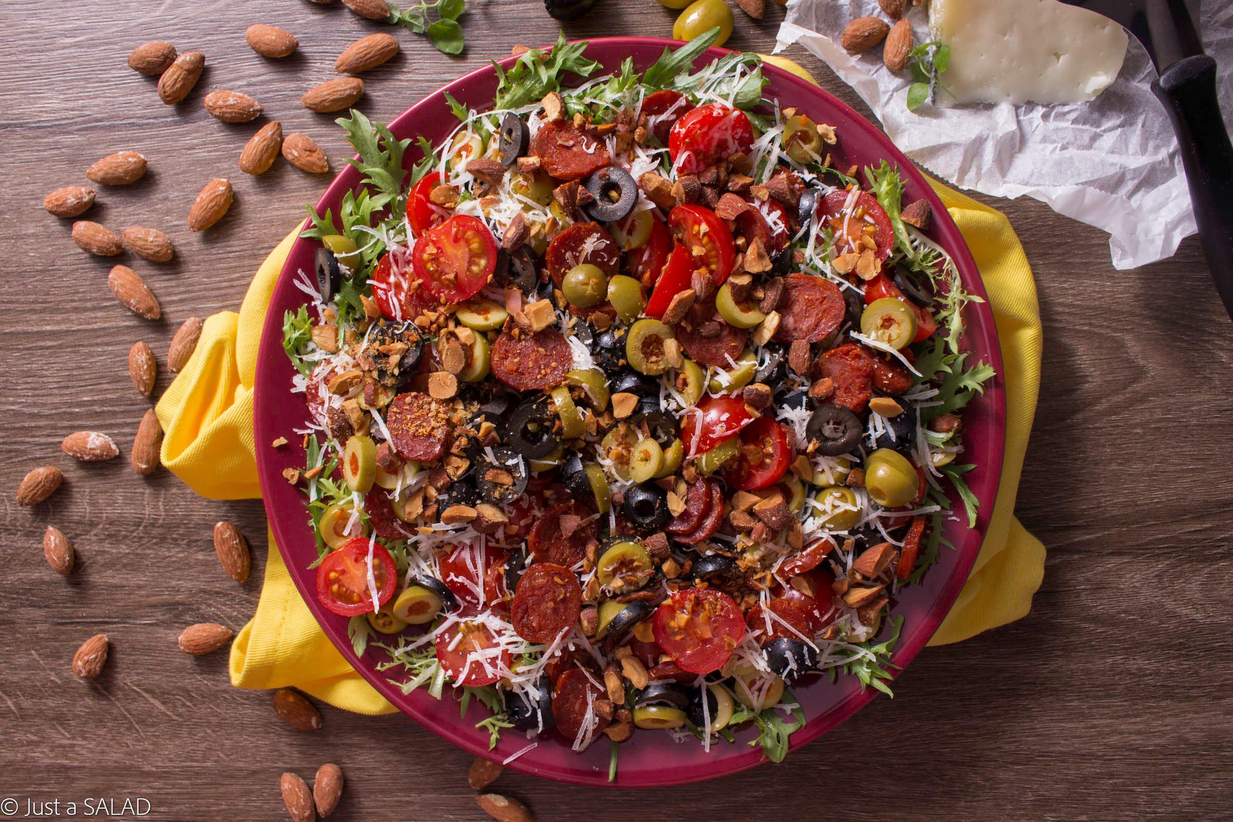 Sałatka z chorizo, owczym serem, oliwkami, pomidorami i migdałami na endywii.