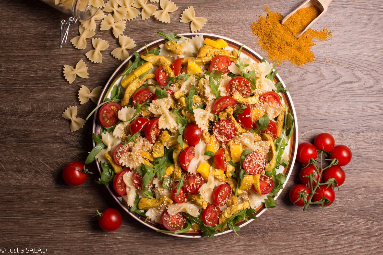 Sałatka z kurczakiem curry, makaronem, rukolą, pomidorkami, mango i sezamem.