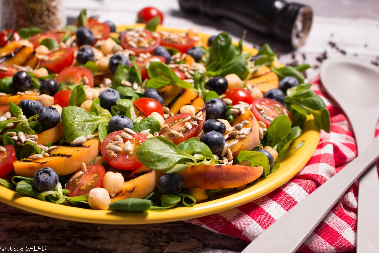 Sałatka z roszponką, ciecierzycą, pomidorami, borówką, brzoskwinią i pestkami słonecznika.
