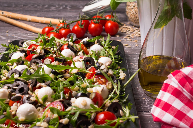 Sałatka z rukolą, makaronem, mozzarellą, pomidorami koktajlowymi i susoznymi oraz pestkami dyni i słonecznika.