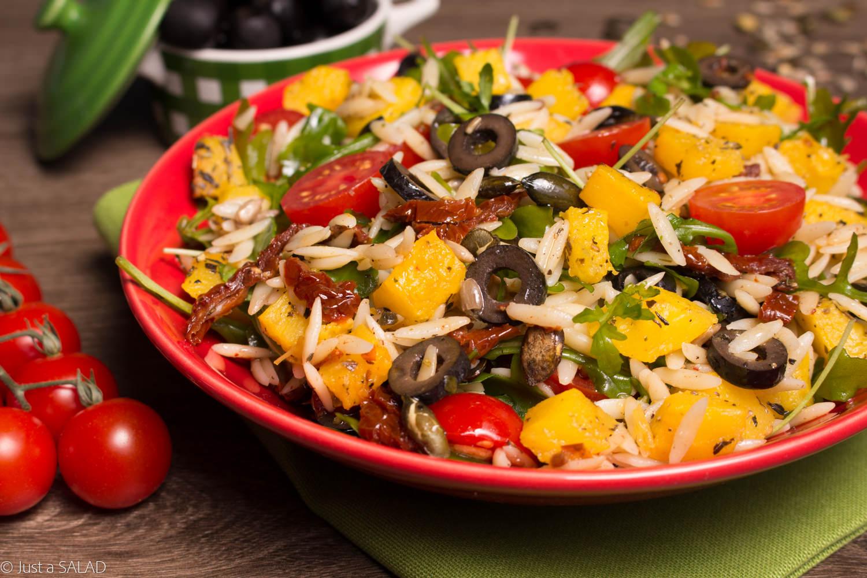 Sałatka z rukolą, dynią, makaronem, pomidorami, oliwkami, pestkami dyni i słonecznika.