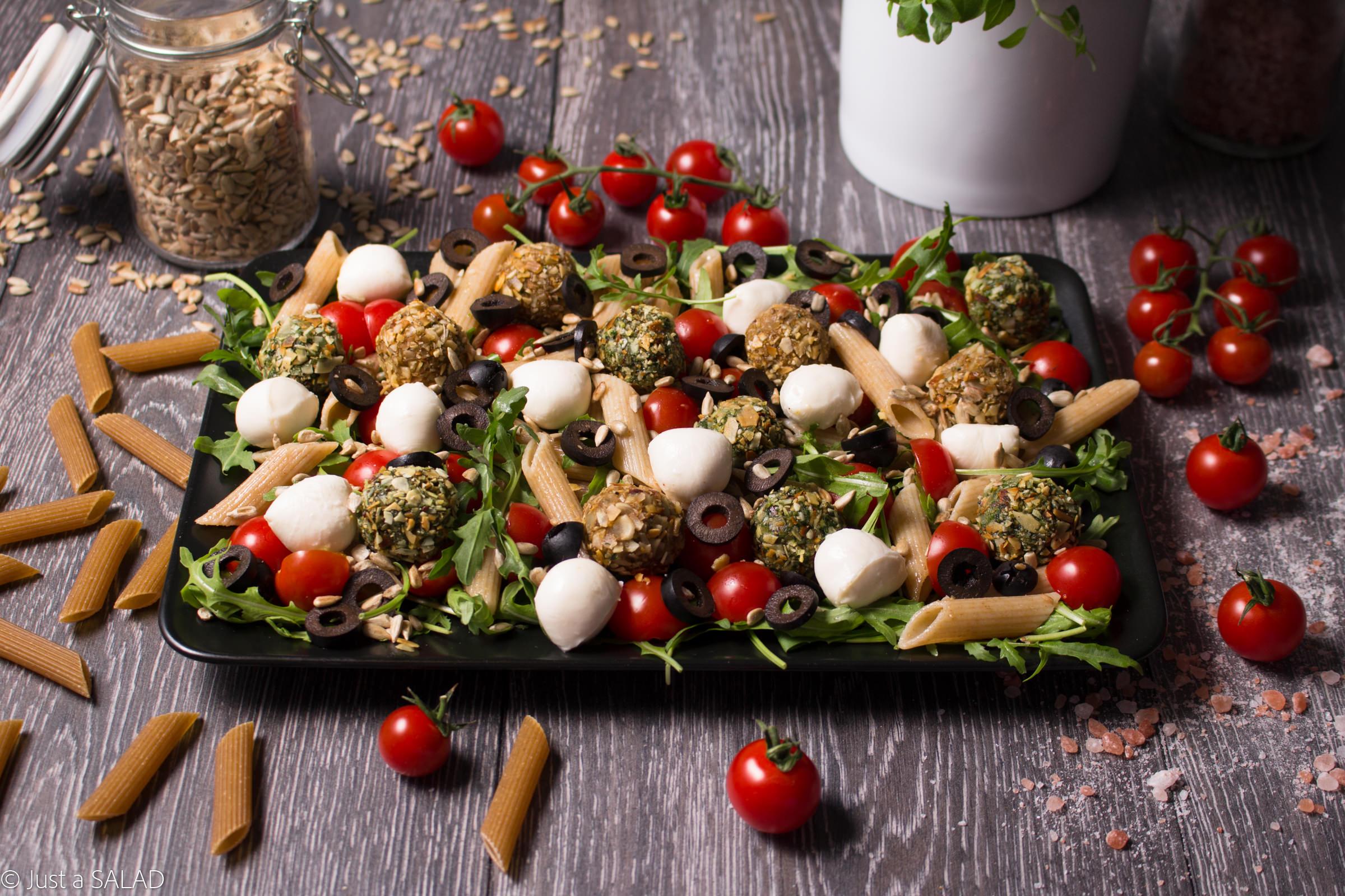 Sałatka z rukolą, makaronem, czarnymi oliwkami, pestkami słonecznika, mozzarellą oraz czerwonymi i zielonymi bombami.