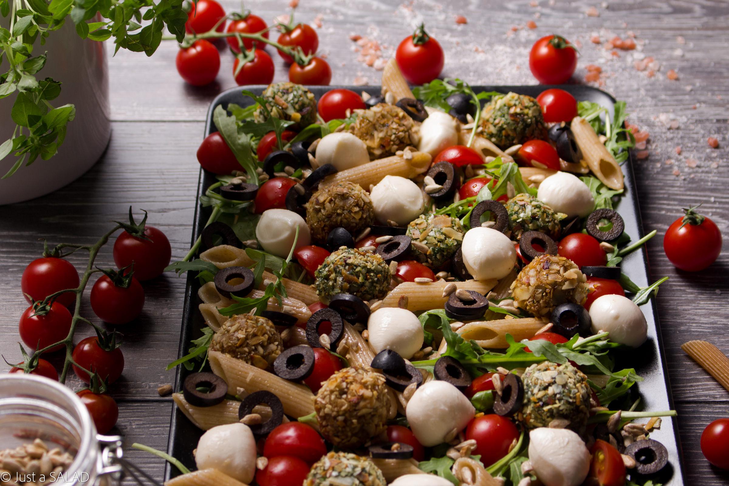 Sałatka z rukolą, makaronem, czarnymi oliwkami, pestkami słonecznika, mozzarellą oraz czerwonymi i zielonymi kulami.