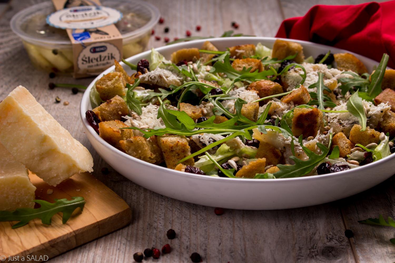 Sałatka z rukolą, sałatą lodową, śledziem, serem grana padano, pestkami słonecznika i domowymi grzankami.