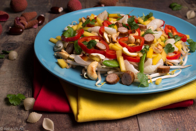 Sałatka z makaronem ryżowym, groszkiem cukrowym, mango, liczi, nerkowcami, kabanosami, kiełkami fasoli mung oraz kabanosami.