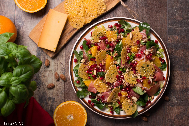 Sałatka z szynką i serem gojrzeającymi, pomarańczami, granatami, migdałami i roszponką.