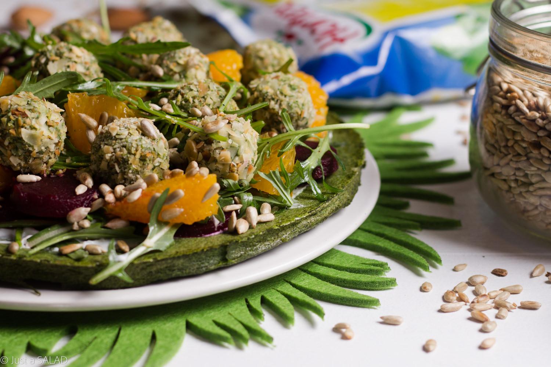 Sałatka na szpinakowym blacie z rukolą, burakami, pomarańczą, pestkami słonecznika i zielonymi kulami.