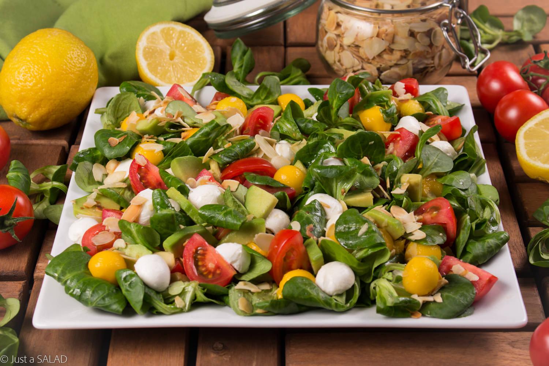 Sałatka z roszponką, mango, pomidorkami, mozzarellą, płatkami migdałowymi i olejem lnianym o smaku cytryny.