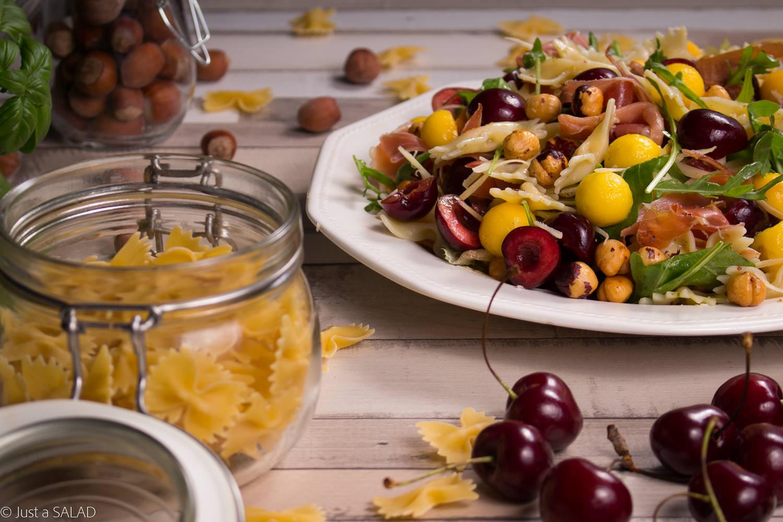 Sałatka z makaronem, rukolą, szynką włoską, czereśniami, mango i orzechami laskowymi.