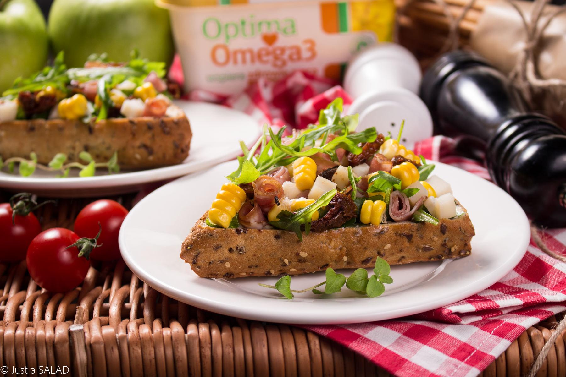 PIKNIK Z OPTIMĄ. Sałatka z rukolą, serem kozim, kindziukiem, suszonymi pomidorami i kukurydzą podana w bułeczce z margaryną ziołową.