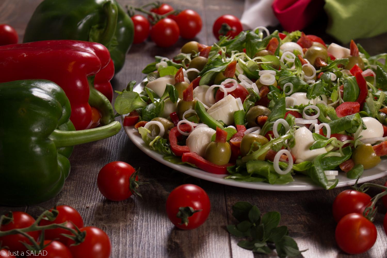 Sałatka z oliwkami nadziewanymi kabanosami, mozzarellą, papryką, pomidorkami i szczypiorkiem.
