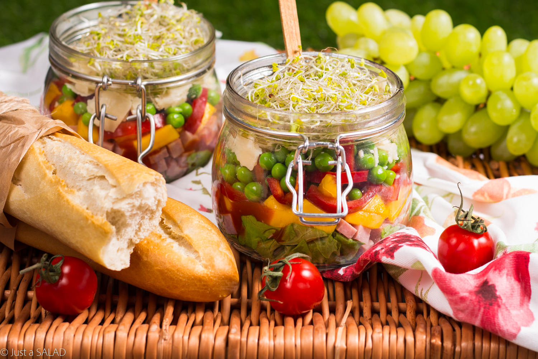 Piknikowy słoiczek. Sałatka piknikowa z kiełbasą krakowską, mango, papryką, groszkiem, serem Grana Padano, kiełkami oraz sosem pomidorowym.