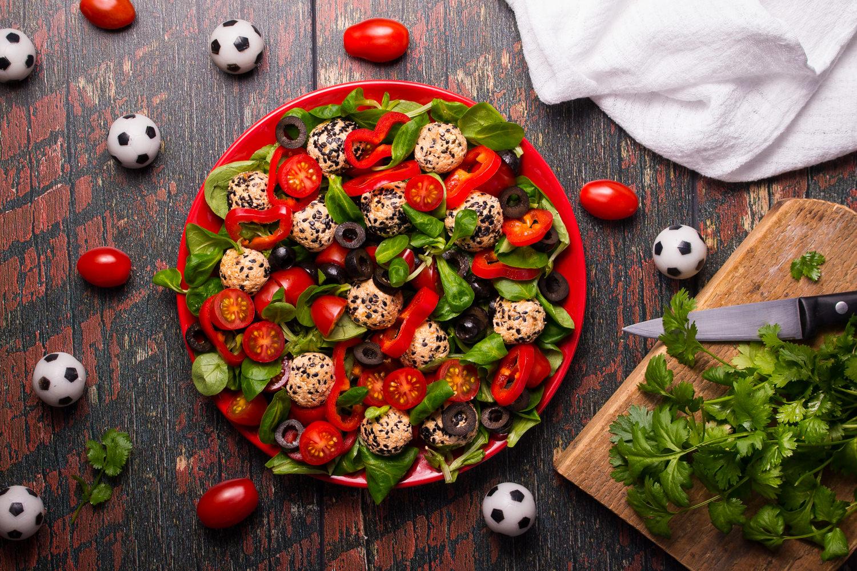 PIŁKA W GRZE. Sałatka z piłeczkami z sera białego, pasty z suszonych pomidorów i żurawiny oraz sezamu, a także pomidorków koktajlowych, papryki i czarnych oliwek.
