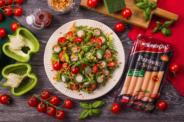 PARÓWKI W OBWODZIE. Sałatka z krążkami z parówkami i zielonego sera typu gouda oraz pomidorków, papryki, prażonej cebuli i rukoli podana z sosem pomidorowym.